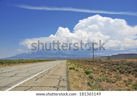 Open road driving in the Western USA with Thunderstorm in the distance - stock photo