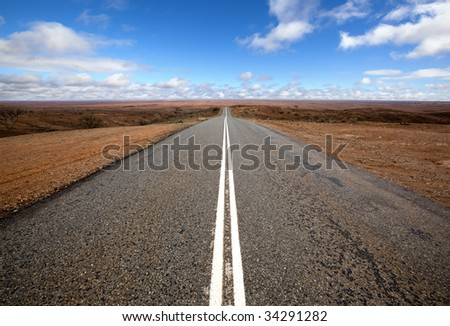 Open road in Australian outback.  Mundi Mundi, west of Silverton, New South Wales.  The horizon is so vast that you can see the curvature of the Earth. - stock photo