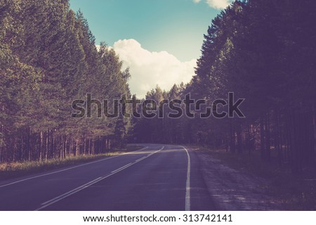 Open Road in future, no cars, auto on asphalt road through green forest, trees, Pines, spruces. clouds on blue sky in summer, sunshine, sunny day. Good weather. bokeh, blurred road vintage background. - stock photo
