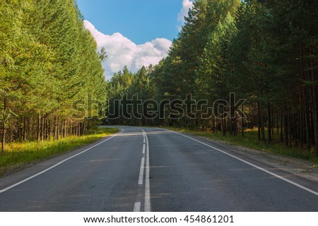Open Road in future, no cars, auto on asphalt road through green forest, trees, pines, spruces. Clouds on blue sky in summer, sunshine, sunny day. Good weather. bokeh, blurred road vintage  - stock photo