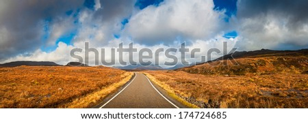 Open road leading through the Scottish Highlands of Glen Coe, snowcapped mountains and dramatic storm broken sky. - stock photo