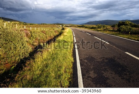 Open road leading through wide field embedded in mystical ambiance on  Isle of Skye, Scotland - stock photo