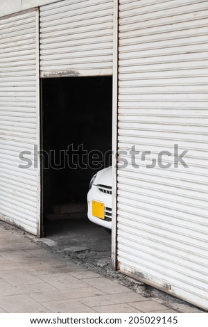 Open roller door of a garage with the front part of a car inside that looks out/The Shy Vehicle - stock photo