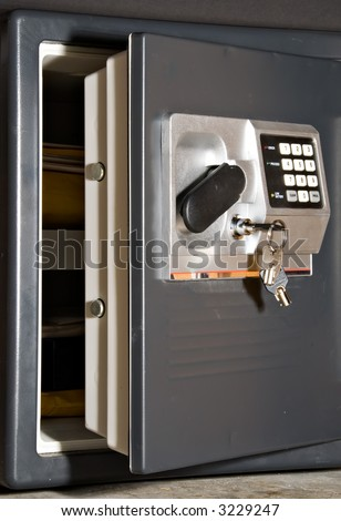 Open safe door with keys hanging on front - stock photo