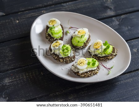 Open sandwiches with cream cheese, quail eggs and celery. Delicious healthy snack or breakfast - stock photo