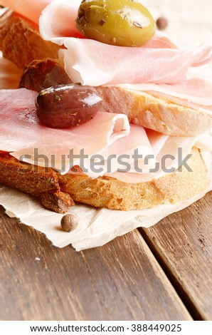 Open sandwiches with jamon and olives on wooden table