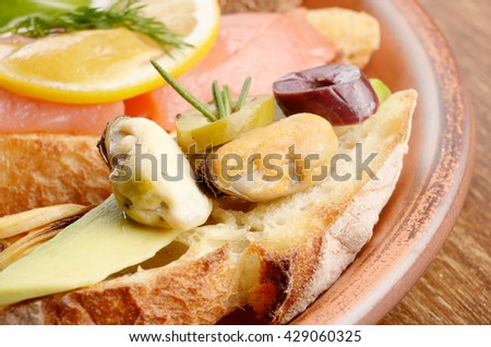 Open sandwiches with salmon and mussels on ceramic plate