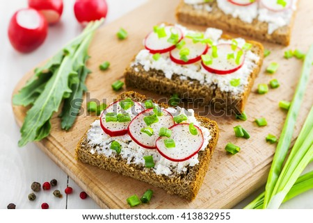 Open sandwiches with soft cream cheese and fresh radish. Summer food on table. Top view, close-up.