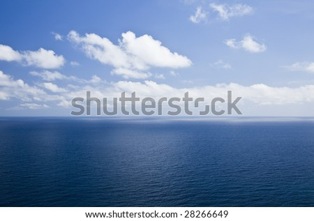 Open seascape under cloudy sky.