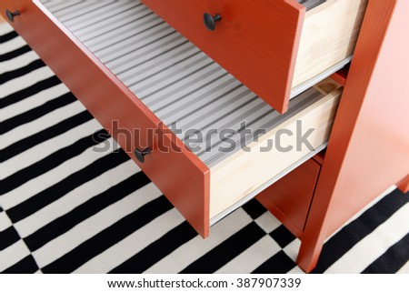 Open shelves of chest of drawers closeup - stock photo