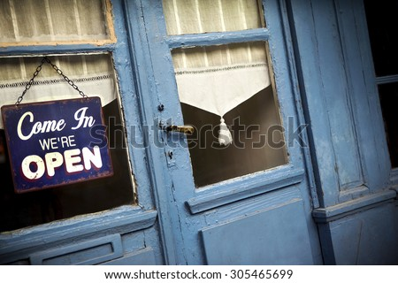 Open sign on the door of an old pub - stock photo