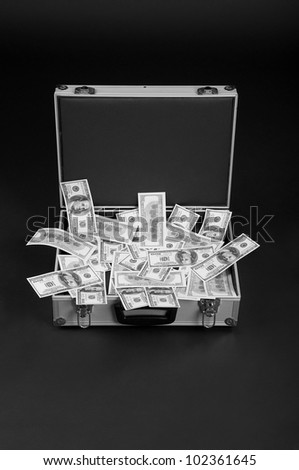 open silver suitcase full of money on a black background