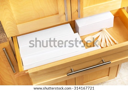 Open six inch kitchen drawer to hold foil, plastic bag and parchment paper containers, think of putting one in when you're renovating, it keeps them off the counter top - stock photo