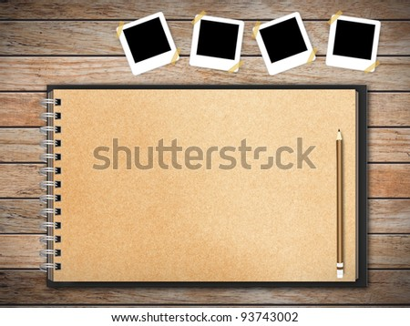 Open sketchbook with a lot of photos on wooden floor - stock photo