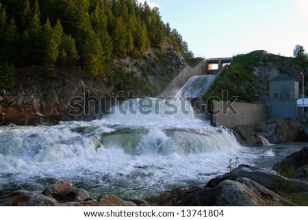 Open spillway and power plant at Cascade Dam, Cascade Idaho - stock photo