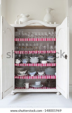 Open storage cupboard showing display of homeware - stock photo