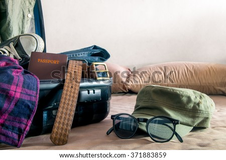 Open suitcase on bed packing for travel - stock photo