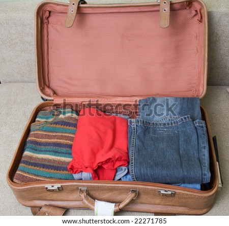 open suitcase with clothing - stock photo