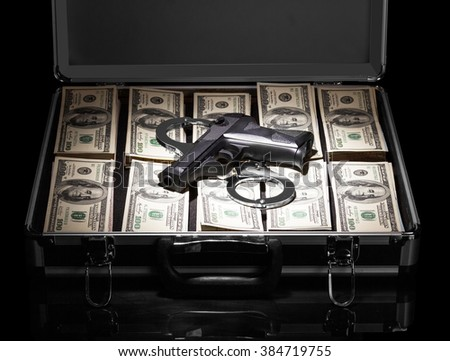 Open suitcase with dollars weapons and handcuffs isolated on a black background.