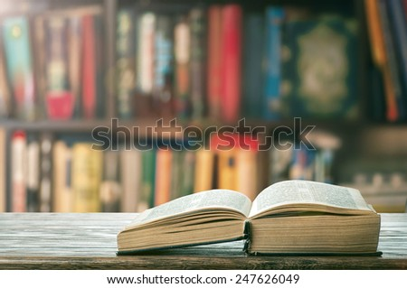Open thick book on the bookshelf - stock photo