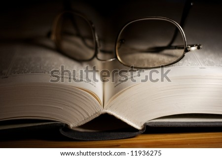 Open thick book with glasses