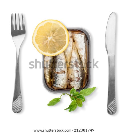 Open tin can full of sardines in olive oil, with lemon and lemon balm on white background. A minimalist expression. - stock photo