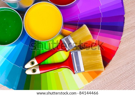 open tin cans with paint and palette on wooden background - stock photo