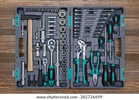 Open toolbox with different instruments on wooden workbench - stock photo