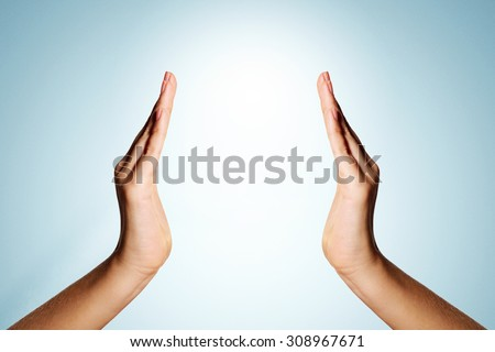 Open two woman hands, palms up isolated on blue background wall - stock photo