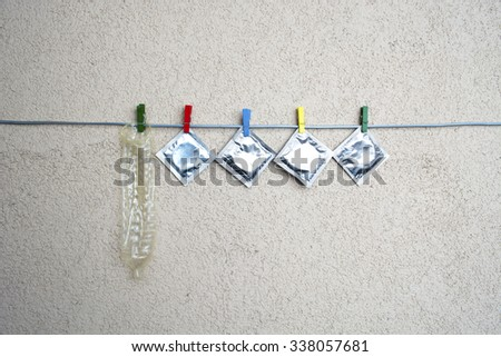 open (used) condom and sealed condoms on colorful clothespins. space for text - stock photo