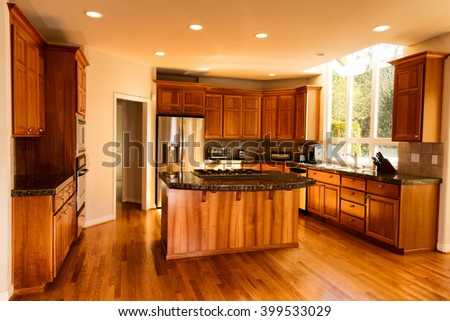 Open view of large home kitchen with all stainless steel appliances  - stock photo