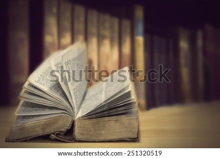 Open vintage books in front of row of other old books - stock photo