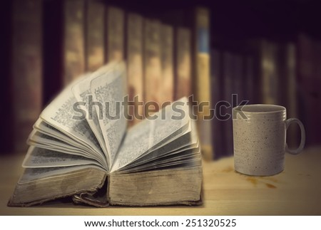 Open vintage books in front of row of other old books, and coffee mug with some spilled coffe on surface - stock photo