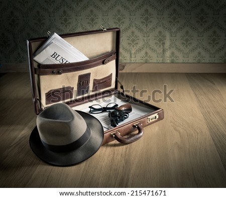 Open vintage leather briefcase with detective hat, revolver gun and newspaper. - stock photo
