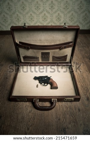 Open vintage leather briefcase with only revolver gun and bullet inside, vintage wallpaper and wooden floor on background. - stock photo