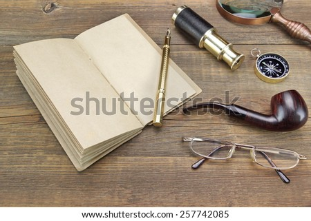 Open Vintage Notebook With Blank Pages, Gold Fountain Pen, Retro Magnifier, Compass, Glasses and Spyglass On Grunge Wooden Table Background - stock photo