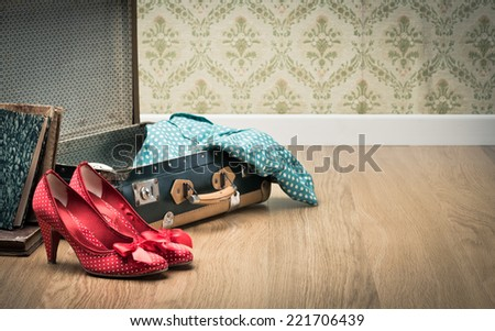 Open vintage suitcase with red shoes and dotted clothing, vintage wallpaper on background.