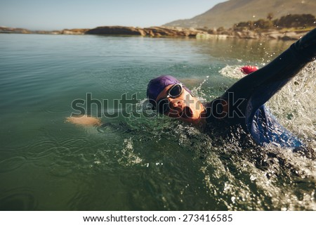 Open water swimming. Male athlete swimming in lake. Triathlon long distance swimming. - stock photo