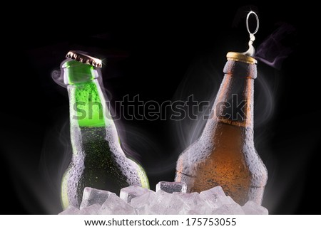 open wet beer bottles on ice isolated on black