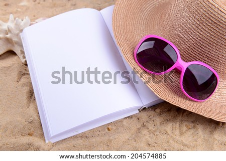 Open white book on sand background - stock photo