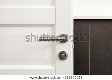 Open white door with metallic handle - stock photo