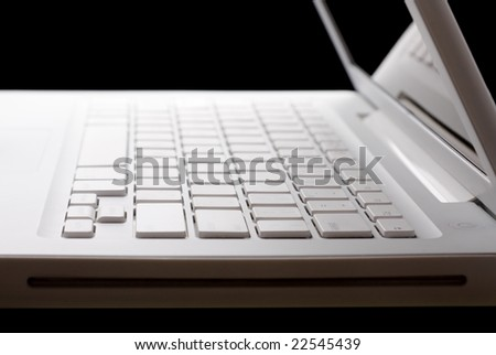Open white laptop with keyboard reflection on display. Black background. Selective focus. Side view.