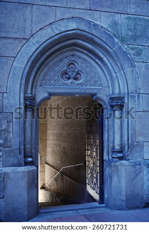 open wide the door to the entrance to the Gothic castle with knights otributami on the stone walls - helmet, sword, sword, shield and wide helical staircase in an old castle Boynetse in Slovakia - stock photo
