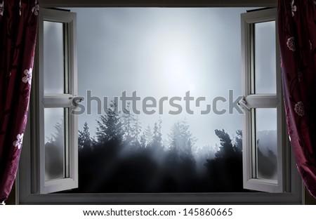 Open window onto moonlight night and tree tops - stock photo