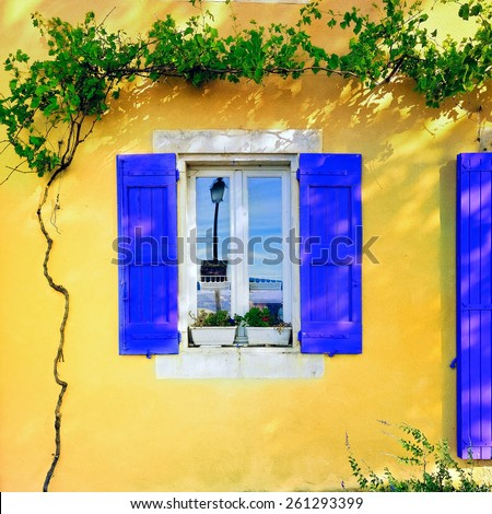 Open window with lavender color wooden shutters  on an ocher color plastered wall on a sunny day. Bonnieux village, Provence, France - stock photo