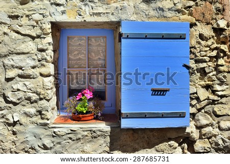 Open window with lavender color wooden shutters  on an stone wall on a sunny day. Provence, France