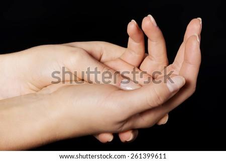 Open woman hands on dark background. - stock photo