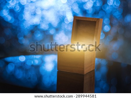 Open wooden gift box with magical light inside, illuminated blue bokeh background - stock photo