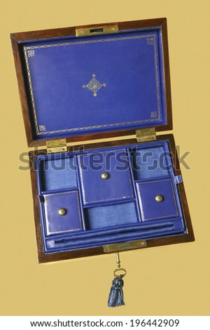 Open wooden jewelry box isolated on yellow. Vertical - stock photo