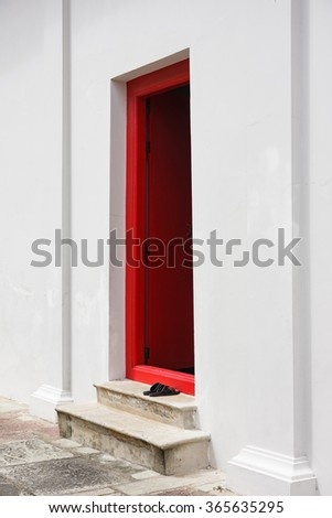 Open wooden red door on White Wall.